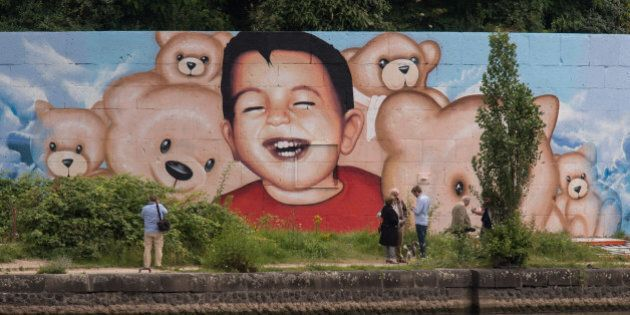People stand in front of a new graffiti by artists Justus Becker and Oguz Sen depicting the drowned Syrian...
