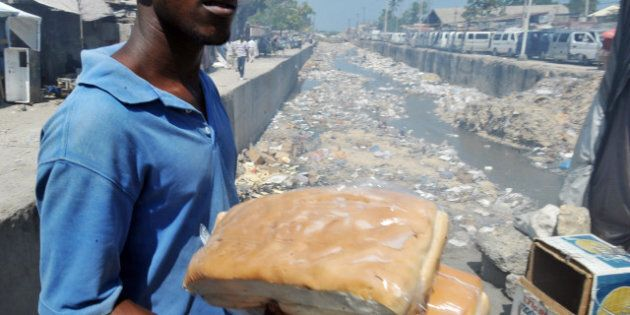 A man carries bread on April 11, 2013 close to a public garbage area in the south of Port-au-Prince....