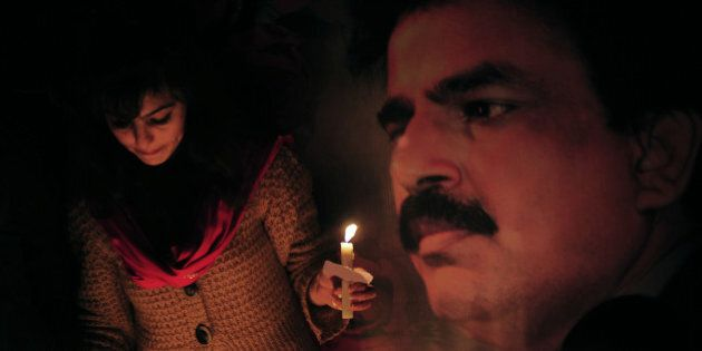 Pakistani civil rights activists light candles during a ceremony on the site of attack on slain Pakistani...