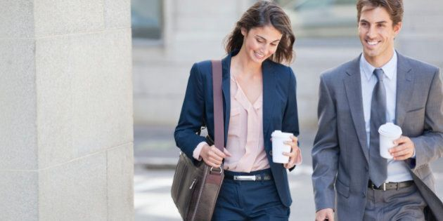 Smiling businessman and businesswoman walking with coffee