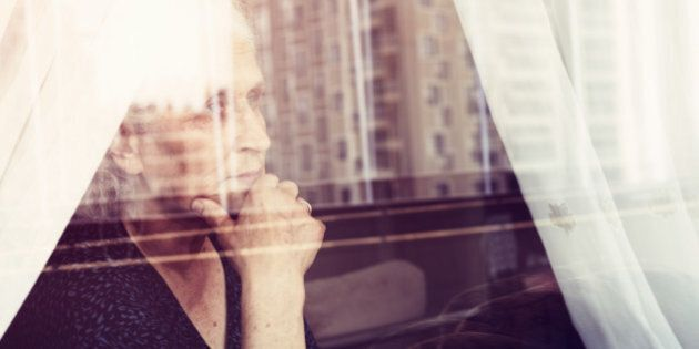 Pensive senior woman looking through a window and