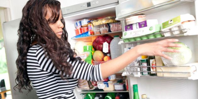 Woman filling the fridge with shopping