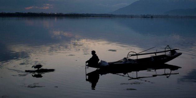 A Kashmiri fisherman prepares to bring to shore his Shikara, or traditional boat, after a days work at...