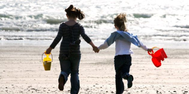Jaquline Reeder, 8 (left) and Rosie Reeder, 7, carry buckets and spades along the beach at Looe, Cornwall, where holiday makers are enjoying the warm sunshine.