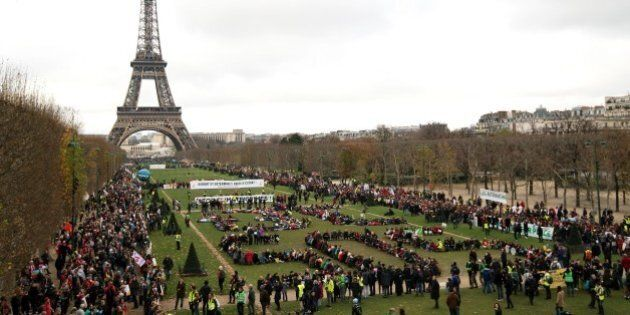 TOPSHOT - Several Non Governmental Organisations (NGO) gather to form a human chain  reading '+3°C SOS' on the Champs de Mars near the Eiffel Tower on December 12, 2015 in Paris on the sidelines of the COP21, the UN conference on global warming.French hosts submit the final version of a global climate-saving pact to negotiators at UN Conference on december 12. The goal is for ministers to approve the agreement by the end of the day but that could be extended one more day. / AFP / ALAIN JOCARD        (Photo credit should read ALAIN JOCARD/AFP/Getty Images)