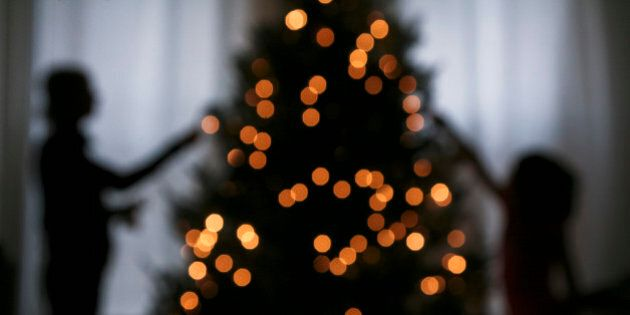 Silhouette of mother and daughter decorating a Christmas tree