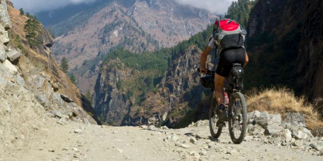 ANNAPURNA REGION, TAL, CENTRAL NEPAL, NEPAL - 2012/12/09: Tourist cycling on a gravel road in Marsyangdi...