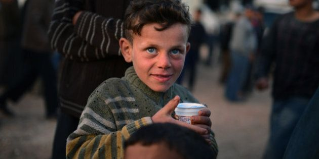 A Syrian boy holds a cup in the refugee camp of Al-Salam in the northern province of Aleppo along the...