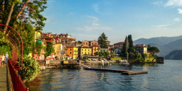 Panoramic view of Lake Como in Northern Italy and the beautiful midieval village of Varenna with people...