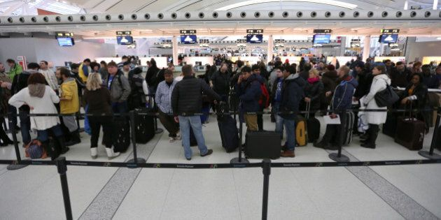 TORONTO, ON - JANUARY 11: Passengers in line up at Terminal 1 waiting to check in and receive boarding...