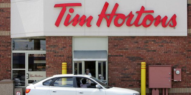 **FILE** A Tim Hortons worker serves a drive-through customer at a Northwest side restaurant in this...