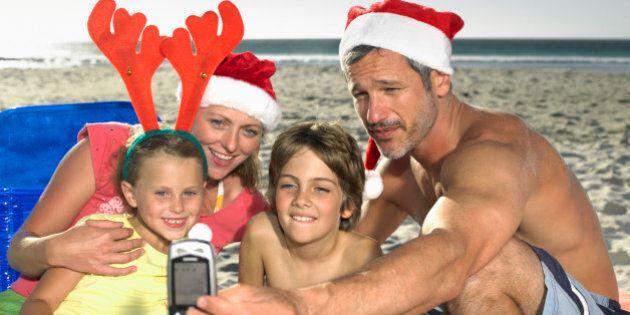 Family of four taking self portrait on beach,