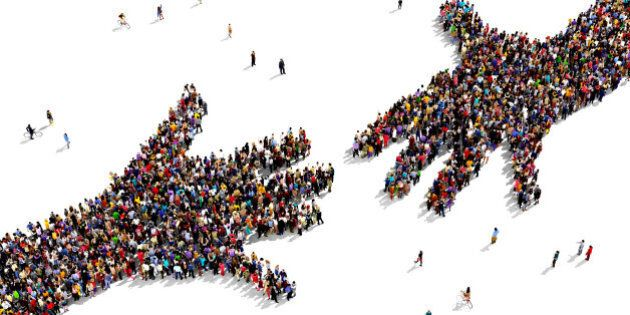 Large group of people seen from above gathered together in the shape of two hands reaching out each other