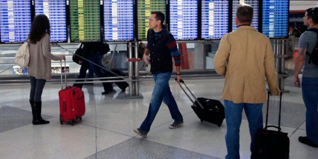 On the busiest travel day of the year, passengers check the departures board in a terminal at Denver...