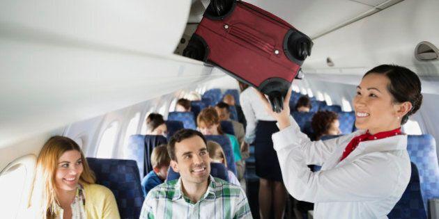 Flight attendant putting luggage in overhead bin in