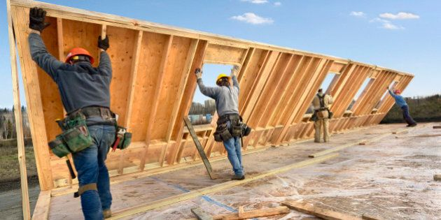Male construction workers raising wall on house, rear