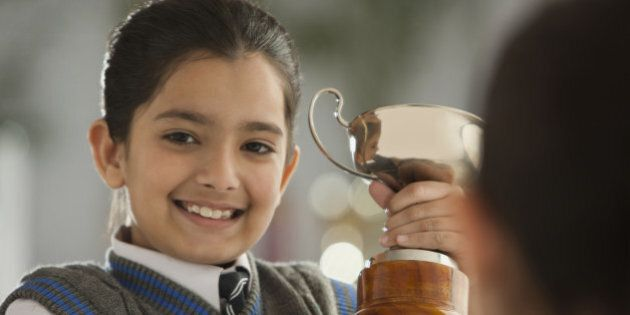 Portrait of schoolgirl (8-9) holding trophy