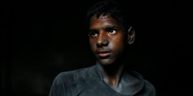 In this Sunday, June 12, 2016, photo, Ridoy, 11, poses for a portrait as he works at a factory that makes metal utensils in Dhaka, Bangladesh. The World Day Against Child Labor, which was initiated in 2002 by the International Labor Organization to highlight the plight of child laborers, is observed across the world on June 12. (AP Photo/A.M. Ahad)