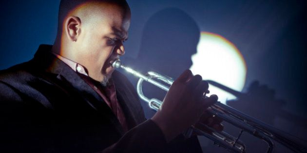 Side view of musican playing trumpet with spotlight shining on him