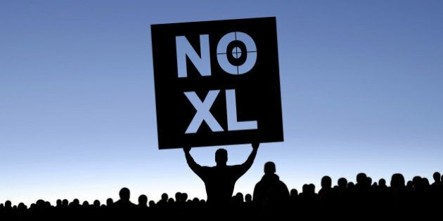 'keystone pipeline protestors in silhouette with man holding 'NO XL' sign, panoramic frame