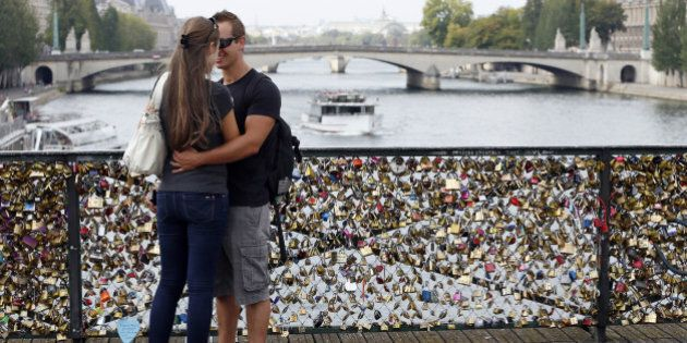 TO GO WITH AFP STORY BY BONIFACE MURUTAMPUNZIA couple kisses at the Pont des Arts where padlocks are attached to the railing, on August 30, 2013 in Paris. Due to security reason authorities consider removing the 'Love locks' that have been attached to the Pont des Arts bridge since 2008 by thousand of lovers.AFP PHOTO / PATRICK KOVARIK        (Photo credit should read PATRICK KOVARIK/AFP/Getty Images)