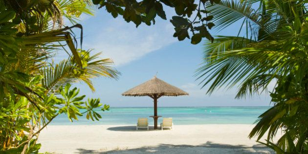 Lounge chairs and a palapa umbrella on the beach at an island resort in South Male Atoll, Maldives.