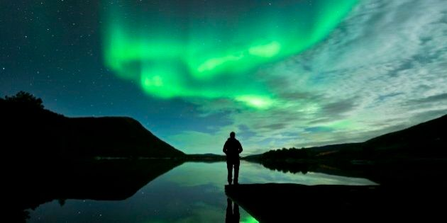 Aurora borealis. Person watching the aurora borealis (northern lights). The aurora borealis is a coloured light display that is visible in the night sky at high latitudes. It occurs when charged and energetic particles from the Sun (the solar wind) are drawn by Earths magnetic field to the polar regions. Hundreds of kilometres up, they collide with gas molecules and atoms, causing them to emit light. Photographed in Hamaroy, Nordland, Norway, in October.