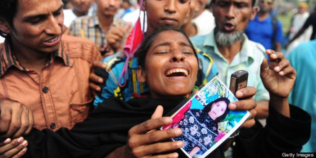 A relative of a missing Bangladeshi garment worker reacts as she gathers at a graveyard for victims of...