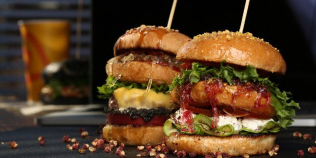 Huge Double hamburger with fresh grilled beef isolated on a black background with pistachios