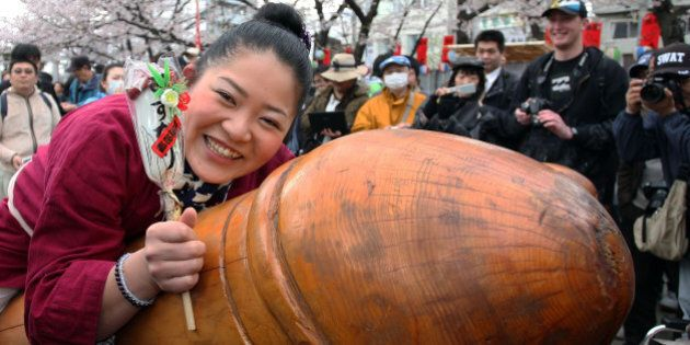 KAWASAKI, JAPAN - APRIL 04: A visitor rides on a wooden phallic figure during the Kanamara Festival, or the Utamaro Festival, near Wakamiya Hachimangu Shrine on April 4, 2010 in Kawasaki, Japan. The annual feritility festival, held traditionally in the cherry blossom season since the Edo era (1603-1868), is said to encourage fertility and bring harmony to married couples. In recent times the festival has raised awareness of AIDS prevention. (Photo by Koichi Kamoshida/Getty Images)