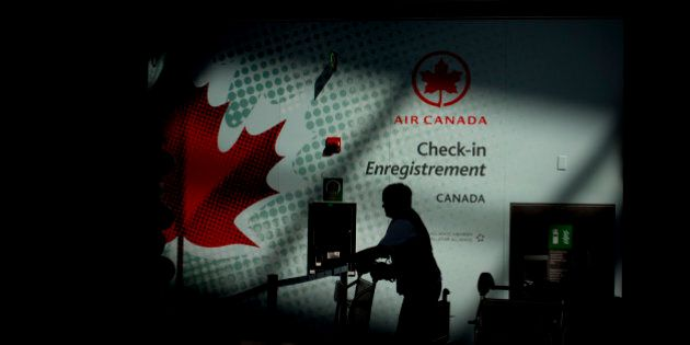 The silhouette of an Air Canada employee is seen pushing a buggy near a check-in counter at Toronto Pearson...