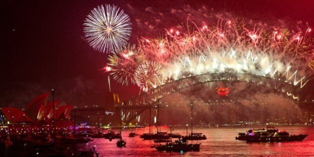 Spectator boats in Sydney Harbour look on as New Year's Eve fireworks erupt over the Sydney Harbour Bridge...