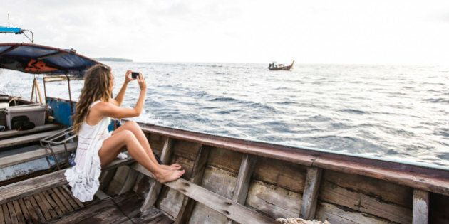 A woman in a white dress taking a photo with her iPhone while riding on a long tail boat to a tropical...