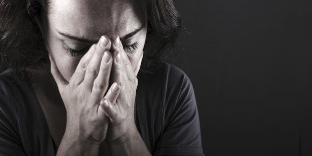 Depressed woman with hands over her face.