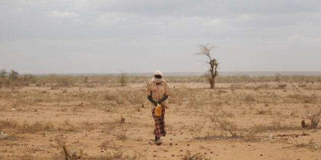 DADAAB, KENYA - JULY 19: A man walks with a water container on the outskirts in the Dagahaley refugee...