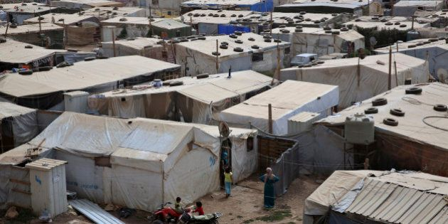 Syrian refugees stand outside their tents at a Syrian refugee camp in the town of Deir Zanoun, Bekaa Valley, Lebanon, Thursday, Sept. 10, 2015. The UNHCR has said there are about 1,150,000 Syrian refugees registered in Lebanon, equal to a quarter of Lebanon's own population of 4.5 million. Beirut estimates there are another 500,000 unregistered Syrians in the country. (AP Photo/Bilal Hussein)
