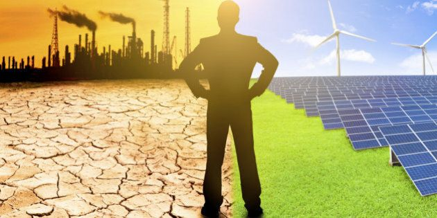 pollution and clean energy concept. businessman watching windmills solar panels and refinery with air