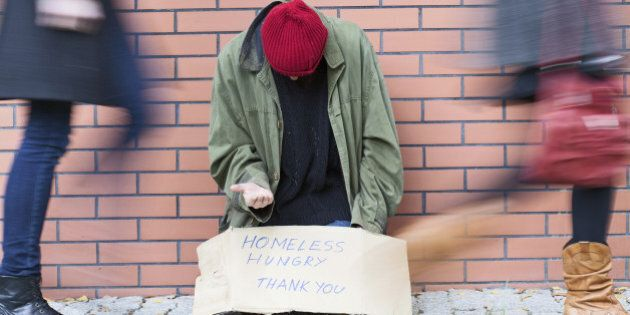 Homeless man sitting on a street passed by