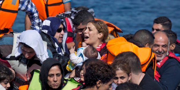 Syrian refugees arrive aboard a dinghy after crossing from Turkey, to the island of Lesbos, Greece, on Sunday, Sept. 20, 2015. A boat with 46 people fleeing Syria sank Sunday in Greece and the coast guard said it is searching for more than 20 others missing off the eastern Aegean island of Lesbos. (AP Photo/Petros Giannakouris)