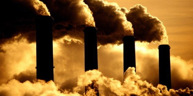 Four industrial chimneys emitting clouds of smoke
