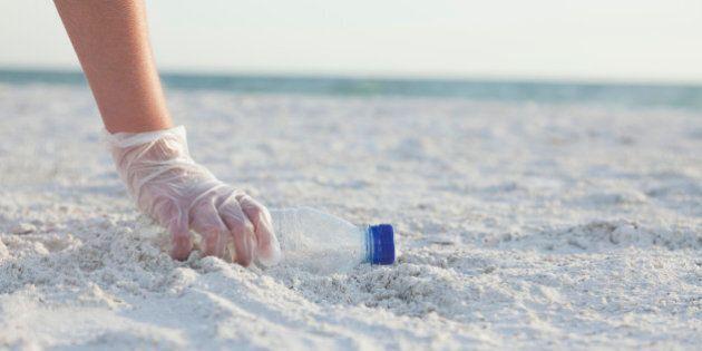 USA, Florida, St. Petersburg, Girl (10-11) collecting plastic bottle on beach
