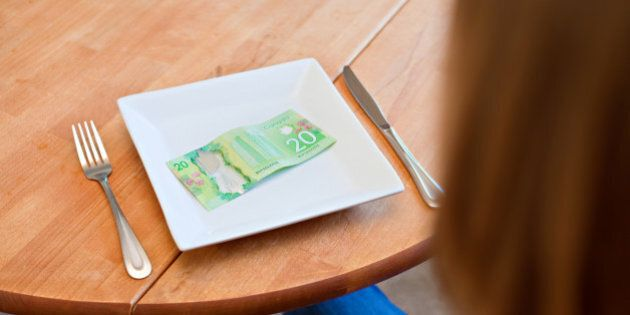 A woman sits at a table with a plate with no food but a $20 Canadian bill