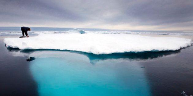 Inuit seal hunter Dines Mikaelsen strokes a dead seal atop a melting iceberg near Ammassalik Island,...