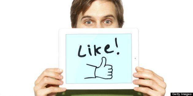 Man holding up like symbol on tablet computer, illustrating social media and sharing.