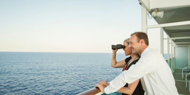 Caucasian couple admiring view from boat