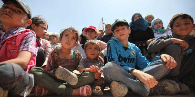 AZRAQ, JORDAN- APRIL 30: Syrian refugee children watch as others perform sports activities in AL- Azraq...