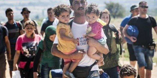 A man carries two children as he walks with other migrants near the southern Serbian village of Miratovac,...