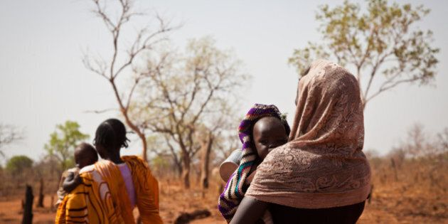 A woman and her child from the Nuba Mountains in Sudan walk outside of the Yida refugee camp registration...