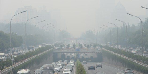 This picture taken on June 23, 2015 shows vehicles running in smog covered streets in Beijing. China's...