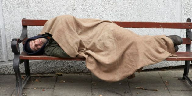 Man sleeping on bench outdoors